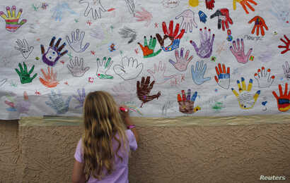 Cali Wilson, 7, draws a rainbow on a poster at the office of U.S. Rep. Gabrielle Giffords in Tucson, Arizona, Jan. 16, 2011.