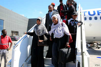 Somali migrants disembark from a plane upon arrival from Libya to be repatriated in their country at Mogadishu International Airport, Feb. 17, 2018. (H.K. Qoyste/VOA)