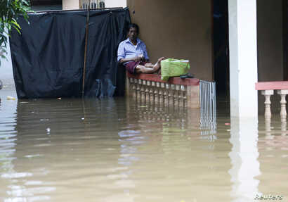 A man sits on a porch fence at his house caught in the flood in Nagoda village in Kalutara, Sri Lanka, May 29, 2017.