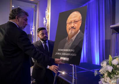 Mongi Dhaouadi (L) and Ahmed Bedier set up an image of slain Saudi journalist Jamal Khashoggi before an event to remember Khashoggi, a columnist for The Washington Post who was killed inside the Saudi Consulate in Istanbul on Oct. 2, in Washington, N