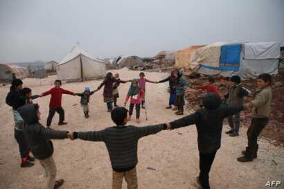 Maya Merhi  stands in the middle as her friends surround her in the Internally Displaced Persons camp of Serjilla in northwestern Syria next to Bab al-Hawa border crossing with Turkey, on Dec. 9, 2018. Eight-year-old Maya, born with no legs