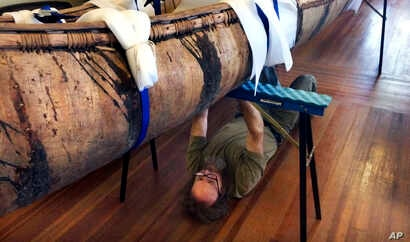 Master canoe builder Steve Cayard prepares one of the oldest-known Native American birch-bark canoes, dated from the mid-1700's, to be displayed at the Pejepscot Museum & Research Center in Brunswick, Maine, Oct. 5, 2017.