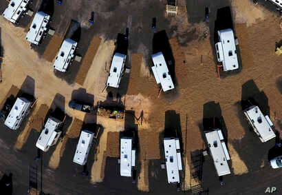 A worker sprays straw around newly setup Federal Emergency Management Agency trailers for residents left homeless by Hurricane Michael in Panama City, Florida, Jan. 24, 2019.