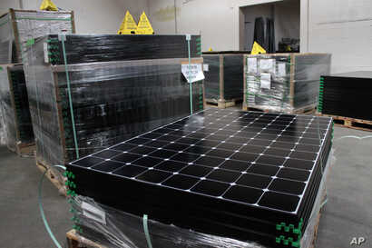 FILE - SunPower solar panels are stacked in Positive Energy Solar's warehouse in Albuquerque, New Mexico, March 9, 2016.