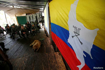 Members of the 51st Front of the Revolutionary Armed Forces of Colombia (FARC) listen to a lecture on the peace process between the Colombian government and their force at a camp in Cordillera Oriental, Colombia, Aug. 16, 2016.