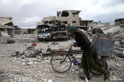 A man walks with his bicycle at a damaged site in the besieged town of Douma, Eastern Ghouta, in Damascus, Syria, March 30, 2018.