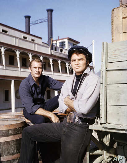 """FILE - Actors Burt Reynolds and Darren McGavin are seen on the set of the TV program """"Riverboat"""" on NBC, Aug. 18, 1959."""