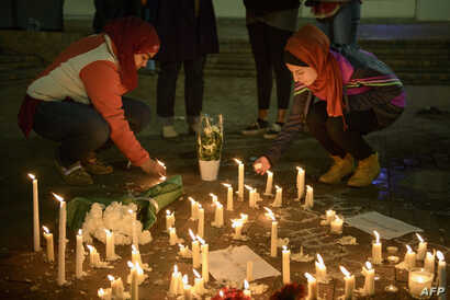 People stand by as a makeshift memorial is made after vigil at the University of North Carolina following the murders of three Muslim students, in Chapel Hill, North Carolina, Feb. 11, 2015.