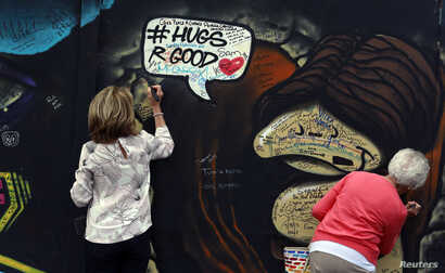 Tourists write messages on a section of the Peace Wall in the loyalist Shankill area of West Belfast in Northern Ireland, Sept. 11, 2015.