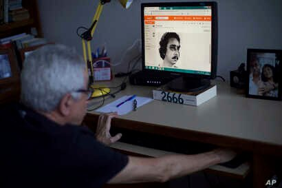 Alvaro Caldas, who was tortured during the dictatorship, shows a photo of himself after being arrested and injured during the Brazilian dictatorship at his home in Rio de Janeiro, Brazil, March 26, 2019.