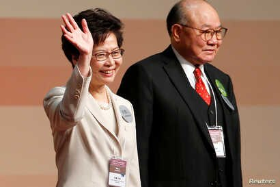 Carrie Lam waves after she won the election for Hong Kong's next Chief Executive as Woo Kwok-hing stands next to her in Hong Kong, March 26, 2017.