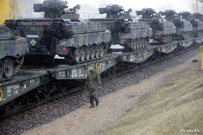 FILE - A German army soldier walks past Marder infantry fighting vehicles at the railway station in Sestokai, Lithuania, Feb. 24, 2017.
