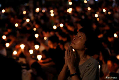 FILE - A woman reacts during a candlelight vigil to mark the 28th anniversary of the crackdown of the pro-democracy movement at Beijing's Tiananmen Square in 1989, at Victoria Park in Hong Kong, China June 4, 2017.
