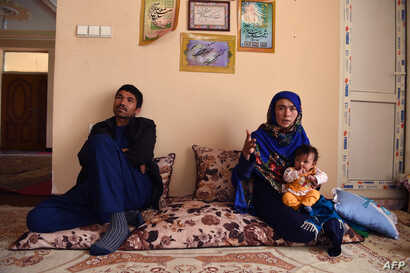 Afghan mother Jahantab Ahmadi, right, 25, holds her youngest child during an interview with AFP as her husband Musa Mohammadi, 27, looks on at a house in Kabul, March 24, 2018.