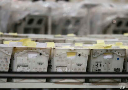 Boxes sit on tables at the Palm Beach County Supervisor of Elections office during a recount, Nov. 14, 2018, in West Palm Beach, Florida.