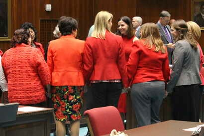 Female members of the Arizona House, from Republican and Democratic parties, hold hands to express support for Rep. Michelle Ugenti-Rita, center facing camera, as the House prepares to vote to possibly expel a member for sexual harassment in Phoenix,...