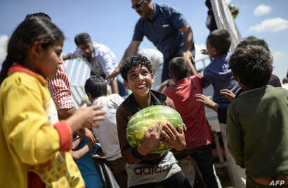 TOPSHOTSA Syrian child holds a watermelon after they were distibuted near the Akcakale crossing gate between Turkey and Syria at Akcakale in Sanliurfa province on June 16, 2015.  Some 23,000 people have fled from Syria to Turkey between June 3 and 15...