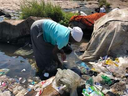 A woman is seen washing clothes in the Mukuvisi River in Harare, Zimbabwe, Sept. 11, 2018, as water shortages persist, what experts say is fueling the spread of cholera. (C. Mavhunga/VOA)