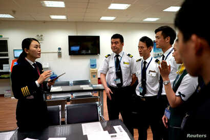 Captain Han Siyuan, 30, gets ready before her plane takes off at an office of Spring Airlines in Shanghai, China, Oct. 18, 2018.