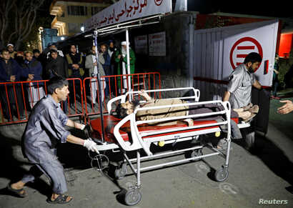 Hospital workers carry an injured person to a hospital after a suicide attack in Kabul, Afghanistan, Nov. 20, 2018.