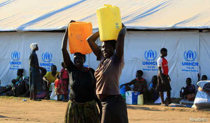 FILE - Women who fled fighting in South Sudan carry water in plastic container on arrival at Bidi Bidi refugee's resettlement camp near the border with South Sudan, in Yumbe district, northern Uganda, Dec. 7, 2016.