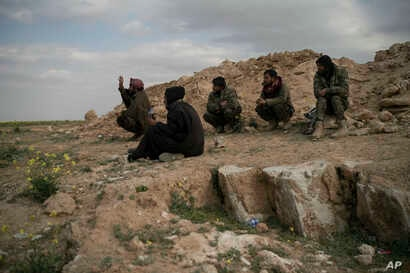 FILE - U.S.-backed Syrian Democratic Forces (SDF) fighters sit atop a hill in the desert outside the village of Baghoz, Syria, Feb. 14, 2019.