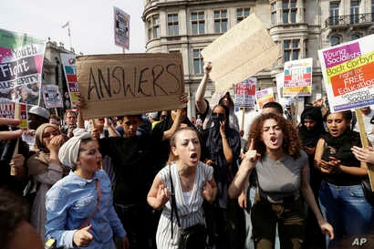 """Demonstrators demand justice for the victims of the recent deadly apartment block fire at Grenfell Tower, after marching to parliament in  London, June 21, 2017. The mass """"Day of Rage"""" demonstration is timed to coincide with the state opening of parl"""