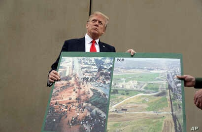 President Donald Trump holds an image of the border area as speaks during a tour as he reviews border wall prototypes, March 13, 2018, in San Diego, as Rodney Scott, the Border Patrol's San Diego sector chief, helps hold the photo.