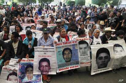 FILE - Relatives of 43 missing students missing since they were taken by local police in September 2014 hold photos of their loved ones, April 24, 2016. Mexico's President Enrique Pena Nieto signed a law Thursday aimed at addressing the country's un...
