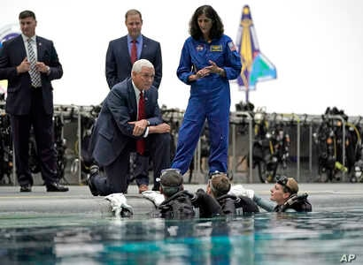 Vice President Mike Pence kneels as he listens to astronaut Suni Williams, right, talk with astronaut candidates in the pool at NASA's Johnson Space Center in Houston, Aug. 23, 2018.