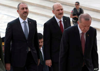 Justice Minister Abdulhamit Gul, left, and Interior Minister Suleyman Soylu, second left, follow President Recep Tayyip Erdogan during a ceremony at the mausoleum of Mustafa Kemal Ataturk, founder of modern Turkey, in Ankara,  Aug. 2, 2018.