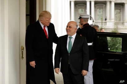 President Donald Trump, left, greets Iraqi Prime Minister Haider al-Abadi upon his arrival to the White House in Washington, March 20, 2017.