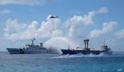 FILE - A Taiwan Coast Guard ship, left, and cargo ship take part in a search-and-rescue exercise off of Taiping island in the South China Sea, Nov. 29, 2016.