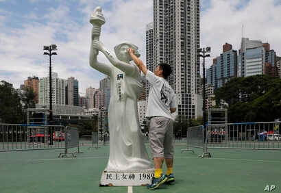 A man wipes the face of a statue of the Goddess of Democracy at Hong Kong's Victoria Park Monday, June 4, 2018.