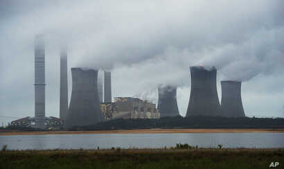 The coal-fired Plant Scherer is shown in operation early Sunday, June 1, 2014, in Juliette, Ga. The Obama administration unveiled a plan Monday to cut carbon dioxide emissions from power plants by nearly a third over the next 15 years.