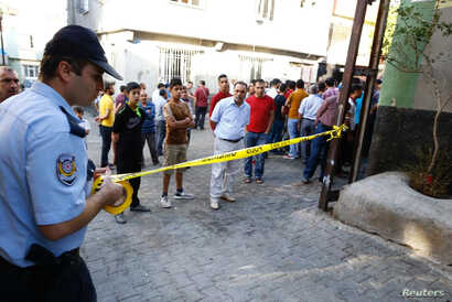 A police officer secures the scene of an explosion where a suspected suicide bomber targeted a wedding celebration in the Turkish city of Gaziantep, Turkey, Aug. 21, 2016.
