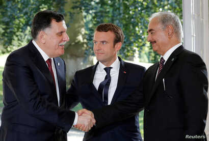 French President Emmanuel Macron stands between Libyan Prime Minister Fayez al-Sarraj (L), and General Khalifa Haftar (R), commander in the Libyan National Army (LNA), who shake hands after talks over a political deal to help end Libya's crisis in ...