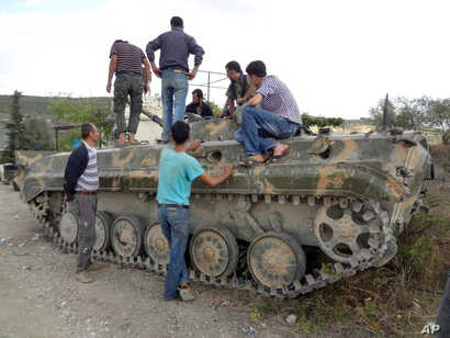 This citizen journalism image provided by Edlib News Network shows Free Syrian Army fighters checking a tank that was captured from the Syrian Army, Khirbet al-Jouz, Idlib, Syria, October 7, 2012.
