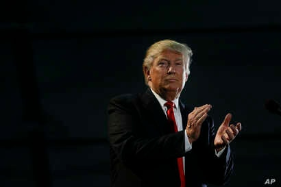 Republican presidential candidate Donald Trump applauds during a rally, Thursday, June 2, 2016.