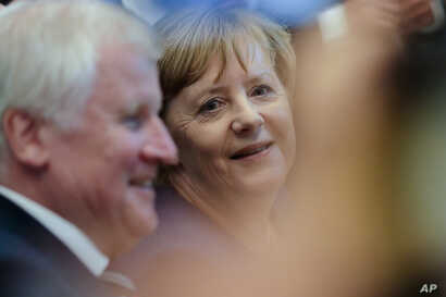 Angela Merkel, center, German Chancellor and Christian Democratic Union, CDU, party chairwoman and Bavarian state governor and Christian Social Union, CSU, party chairman Horst Seehofer, left, attend the parliamentary caucus of Merkel's conservative ...