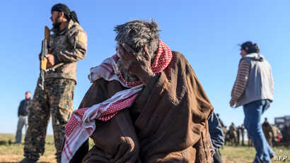 A member of the Kurdish-led Syrian Democratic Forces (SDF) stands by, left, as a man sits with his head in his hand, after leaving the Islamic State (IS) group's last holdout of Baghuz, in the eastern Syria, March 1, 2019.