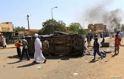 A police car flipped over and damaged by mourners is seen near the home of a demonstrator who died of a gunshot wound sustained during anti-government protests in Khartoum, Sudan, Jan. 18, 2019.