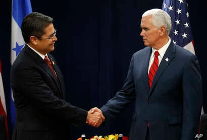 FILE - Honduras' President Juan Orlando Hernandez, left, shakes hands with U.S. Vice President Mike Pence during a conference on Prosperity and Security in Central America in Miami, Florida, June 15, 2017.