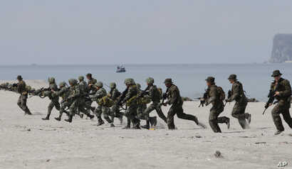 FILE - U.S. and Philippine marines storm the beach to simulate a raid during the joint U.S.-Philippines military exercise at the Naval Training Exercise Command, a former US naval base, and facing the South China Sea at San Antonio township, Zambales...