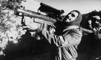FILE - An Afghan guerrilla handles a U.S.-made Stinger anti-aircraft missile in this photo made between November 1987 and January 1988.