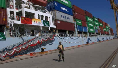 A Pakistan soldier stands guard while a loaded Chinese ship prepares to depart Gwadar port, about 700 kilometers (435 miles) west of Karachi. Pakistan, Nov. 13, 2016.