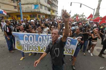 """Demonstrators shouting slogans hold a banner with a message that reads in Spanish: """"Colon united for the cause"""" in Colon, Panama, March 13, 2018."""