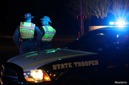 Texas state troopers keep watch at a checkpoint as nearby law enforcement personnel investigate an incident that they said involved an incendiary device in the 9800 block of Brodie Lane in Austin, Texas, March 20, 2018.
