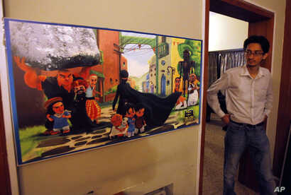 """FILE - A Pakistani man looks at a poster of the animated """"Burka Avenger"""" series on display at an office in Islamabad, Pakistan, July 24, 2014."""