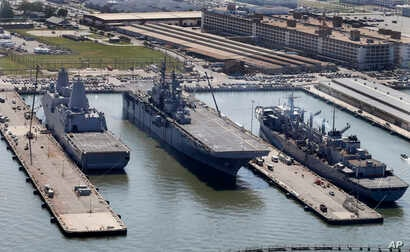 The amphibious assault ship USS Wasp (center) sits pierside along with support ships at Naval Station Norfolk in Norfolk, Va., April 27, 2016.